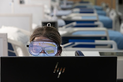 © Licensed to London News Pictures . 15/04/2020. Manchester, UK. A clinician wearing goggles and a face mask operates a computer on a ward of the Nightingale NW Hospital . The National Health Service has built a 648 bed field hospital for the treatment of Covid-19 patients , at the historical railway station terminus which now forms the main hall of the Manchester Central Convention Centre . The facility is due to fully open this week (ending Friday 17th April 2020 ) and will treat patients from across the North West of England , providing them with general medical care and oxygen therapy after discharge from Intensive Care Units . Photo credit : Joel Goodman/LNP