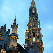 A dusk photo of the main tower of the Hotel de Ville in the Grand Place, Brussels. Originally the city's central market place, the Grand-Place is now a UNESCO World Heritage site. Ornate buildings line the square, including guildhalls, the Brussels Town Hall, and the Breadhouse, and seven cobbelstone streets feed into it.