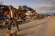 A man walking his dog past debris from teh March 11 tsunami, Ishinomaki, Miyagi Prefecture, Japan, May 5, 2011. Almost two months after the devastating earthquake and tsunami the reconstruction has barely begun.