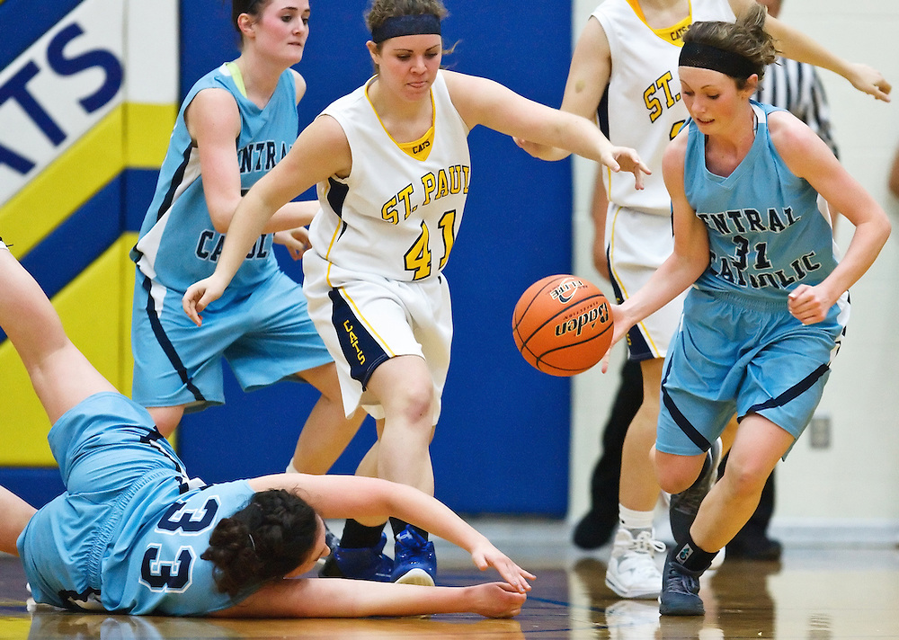 Central Catholic's McKenna Kime scoops up a ball intended for St. Paul's Megan Allen (41) knocked loose by Meghan Krajicek (33) in Tuesday's game at St. Paul High School. The Crusaders won 43-31.(Independent/Matt Dixon)