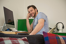 Mid adult man working on computer in living room and smiling, Munich, Bavaria, Germany