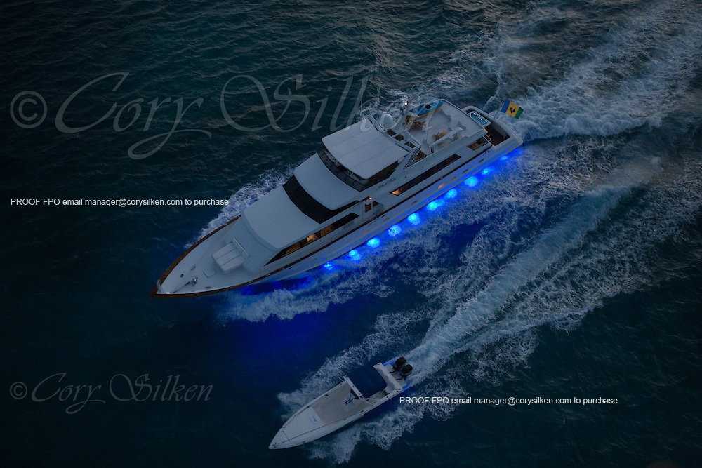 Aerial helicopter shoot of Motor yacht Island time in Cat Cay, Bahamas, featuring Ocean LED lights at dusk.