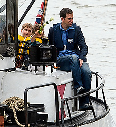 © Licensed to London News Pictures. 22/06/2016. London, UK.  A barge carrying BRENDAN COX with his children CUILLIN and LEJLA holding roses as they watch a memorial boat of flowers being moored in Westminster,  ahead of a memorial service to mark the life of Labour MP for Batley and Spen, Jo Cox, who would have turned 42 today.   Photo credit: Ben Cawthra/LNP