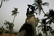 Children climbing a statue of Nuno Tristao, Portuguese explorer. These statues of the Portuguese colonial days were removed from their places all over the country with independence, and now rest abandoned in the margins of the river Cacheu.