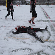 Michael Cognetta, New Canaan, celebrates victory by making a snow angel after the New Canaan Rams Vs Darien Blue Wave, CIAC Football Championship Class L Final at Boyle Stadium, Stamford. The New Canaan Rams won the match in snowy conditions 44-12. Stamford,  Connecticut, USA. 14th December 2013. Photo Tim Clayton
