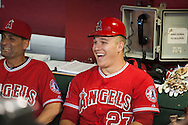 Angels' outfielder Mike Trout laughs as he tries on first base coach Alfredo Griffin's helmet before the start of Halos' game against the Diamondbacks at Chase Field Thursday.