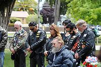 Lowered heads during a Memorial Day prayer at the World War II Memorial Rose Garden in Salinas.