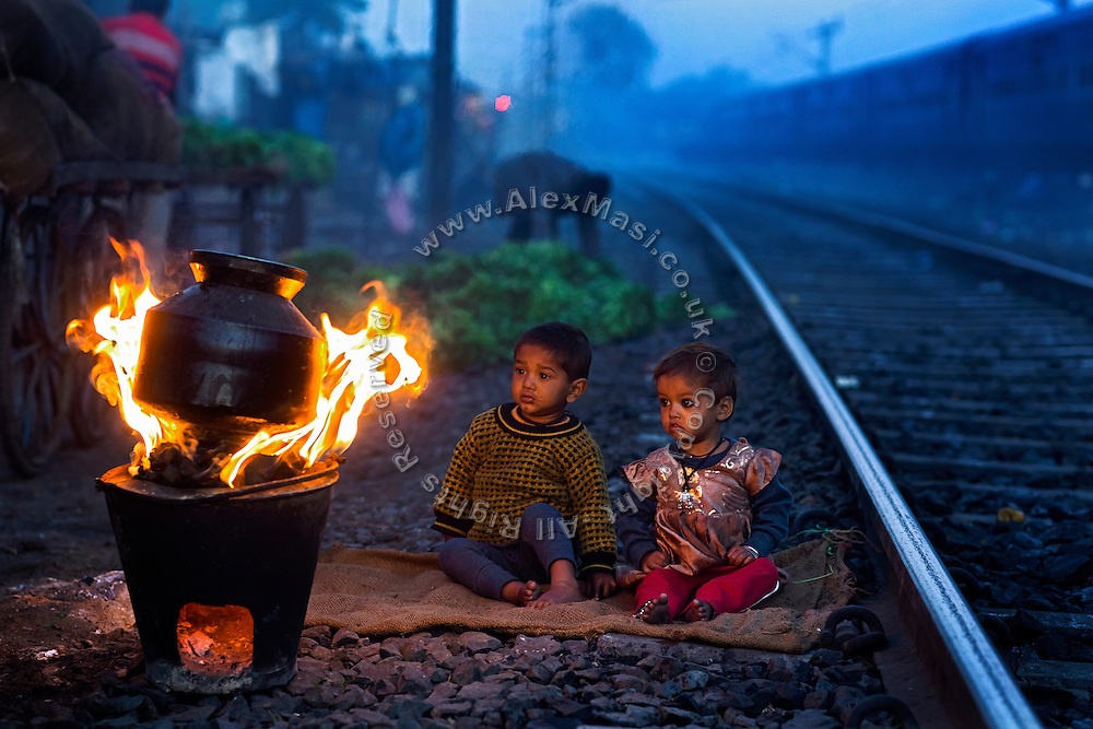 Warming up during a cold morning, two young siblings are sitting by the fire in front of their home by the railway tracks in New Arif Nagar, one of the water-affected colonies standing next to the abandoned Union Carbide (now DOW Chemical) industrial complex, site of the infamous 1984 gas tragedy in Bhopal, Madhya Pradesh, central India.