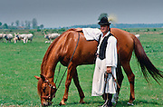 Traditional Csikos Cowboy with his horse on the Great Hungarian Plains in Bugac, Hungary.