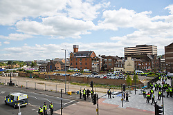 Luton, UK. 27th June, 2015. Police officers are positioned between a march by far-right group Britain First and a counter-protest by local residents and anti-racist activists from Unite Against Fascism. A large police presence kept the two groups apart.