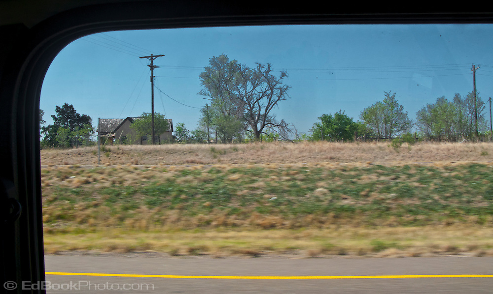 a lone farmhouse in flat rural west Texas along interstate 20 panorama framed by a Mini Cooper automobile window