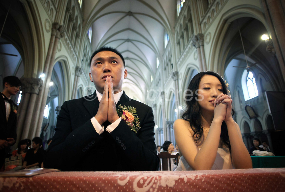 Coca Dai and Juan Juan pray during their wedding ceremony at the Xujiahui Catholic Church in Shanghai, China on 23 May 2009.  A hip street artist and a recent Catholic convert, Mr. Dai is one of many young Chinese embracing religion, perhaps to fill the lack of belief and ideology in an authoritarian communist China that embraces the most extreme form of capitalism in practice. The Chinese government and the Vatican have a long history of simmering mutual distrust and suspicion, as two parties compete for the control of the Chinese Catholic church, with some 15 million and growing number of faithfuls.  Overall Christians now number over 110 million in China, which makes it the third largest Christian nation in the world.