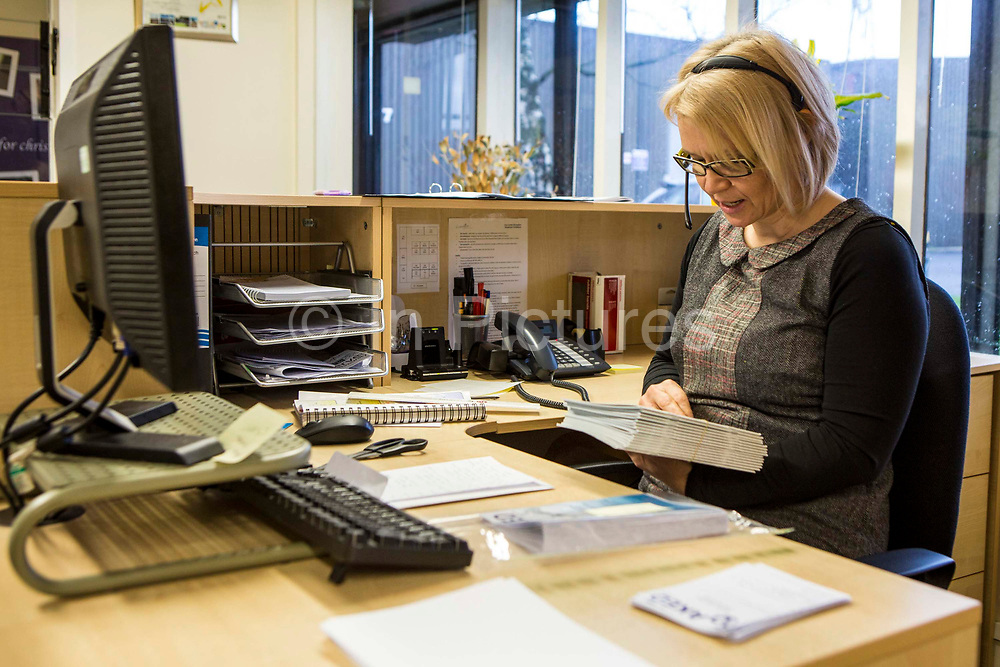 The receptionist at head office. Volunteers from Longton Community Church working to improve the lives of those in need in their local community, Leyland, Lancashire.