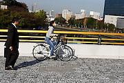 Een vrouw fietst met een mondkapje voor over een brug in Osaka, terwijl een man in pak op weg is naar het werk.