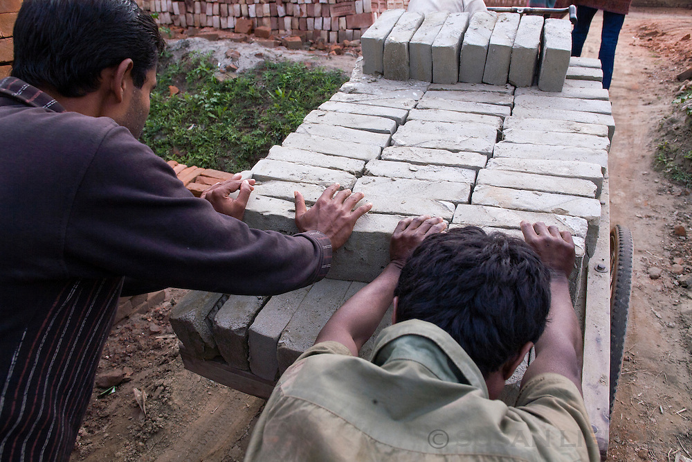Two men at a brick making factory in Bangladesh pushing a cart loaded with bricks ready to be fired in the kiln.