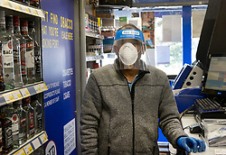 © Licensed to London News Pictures. 19/04/2020. Fetcham, UK. The owner of the Holiday News newsagents shop wears full protective face mask, visor and gloves as he stays open for customers in Fetcham, Surrey. The government have announced that lockdown will continue for another three weeks. The public have been told they can only leave their homes when absolutely essential, in an attempt to fight the spread of the coronavirus COVID-19 disease. Photo credit: Peter Macdiarmid/LNP