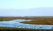 Coastal landscape of salt marsh with boats moored in meandering river drainage channels along the coastline off Faro, Algarve, Portugal