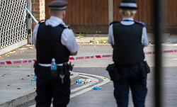 © Licensed to London News Pictures. 11/07/2019. London, UK. Police look on as medical gloves and bloodied bandages remain on the ground in Tellson Avenue, Greenwich where a man in his twenties was stabbed. Police were called at 1440hrs on Wednesday, 10 July to reports of a stabbing. The victim was taken to hospital where he died off his injuries. Photo credit: Peter Macdiarmid/LNP