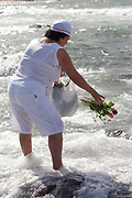 Elderley Brazilian woman making offerings of flowers to the sea in honour of Yemanja. February 2nd is the feast of Yemanja, a Candomble Umbanda religious celebration, where thousands of adherants visit the Rio Vermehlo Red River to pay their respects to Yemanja, the Orixa goddess of the Sea and water.