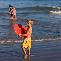 A young boy and his skim board at Hampton Beach in Hampton Beach, New Hampshire.