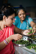 An Indian housewife at home with her mother-in law in New Delhi, slices okra in her kitchen. New Delhi, India