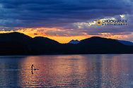 Standup paddleboarders silhouetted by sunset at city beach in Whitefish, Montana, USA