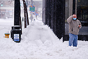 26 JANUARY 2021 - DES MOINES, IOWA: A man waits for a bus on a snow packed street in downtown Des Moines. Workers in Des Moines started cleaning up a record snowfall Tuesday morning. The National Weather Service reports that 10.3 inches of snow fell at Des Moines International Airport Monday, January 25, breaking the daily record of 10 inches for January 25 set in 1895. Many downtown businesses closed for the day because of the snow, since roads throughout central Iowa were snowpacked and hard to drive.        PHOTO BY JACK KURTZ