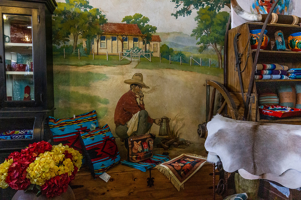 """Historical mural painted on the walls<br /> The Texas Ranch House<br /> Rustic Furniture Store in Sabinal, Texas<br /> <br /> The original """"Ranch House"""" was built in 1938 by Michael Glasscock. During its history it was a cafe, dance hall, and service station. The back room was used as a dance hall from 1938 until the early 1970's, hosting celebrities such as Howard Hughes, Roy Rogers, Dale Evans and John Wayne <br /> <br /> Inside, the original W.R. Dallas lighting fixtures are still prominent and the original mural is still on the walls of the back room, depicting the Glasscock's ranch."""