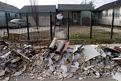 21 December 05. New Orleans, Louisiana.  Post Katrina aftermath. <br /> A santa claus face hangs from a gate in front of a pile of rubble and debris cleared from a house in the devastated 9th ward following Hurricane Katrina.<br /> Photo; ©Charlie Varley/varleypix.com