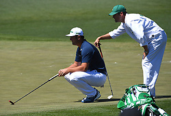 Jon Rahm, left and his caddie, Adam Hayes, right, line up a putt on the 2nd green during the third round of the Masters Tournament at Augusta National Golf Club in Augusta, Ga., on Saturday, April 8, 2017. (Photo by Jeff Siner/Charlotte Observer/TNS) *** Please Use Credit from Credit Field ***