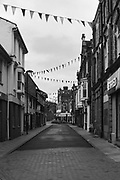 Looking West along lower West Street in Cromer. Bunting decorates Cromer's town center which is nearly deserted in the early morning before the tourists arrive.<br /> <br /> Photo by Jonathan J Fussell, COPYRIGHT 2021