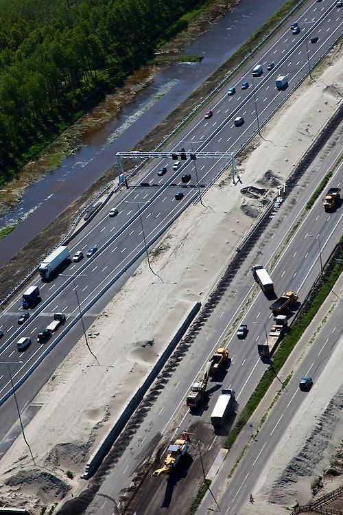 Nederland, Utrecht, Abcoude, 12-05-2009; verbreden van Rijksweg A2 ter hoogte van Abcoude. Om de doorstroming op de A2 structureel te verbeteren wordt de snelweg verbreed van 2x3 naar 2x5 rijstroken. Westelijk van de weg (rechts) Buitenborgh, villapark met recreatiewoningen en de Vinkenveensche Plassen, daarom ligt het nieuwe weggedeelte oostelijk. Het weggedeelte tussen het knooppunt Holendrecht en Maarssen is een van de knelpunten die versneld wordt aangepakt om de economische schade ten gevolge van de files te bepreken. De versnelde aanpak is het mogelijk dankzij een speciale Spoedwet  .Swart collectie, luchtfoto (toeslag); Swart Collection, aerial photo (additional fee required).foto Siebe Swart / photo Siebe Swart