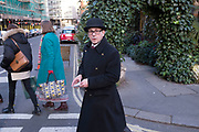Doorman wearing a bowler hat and thick winter coat in Covent Garden, London, UK.