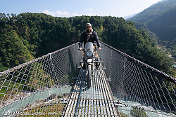 Motorcycle Sherpa's Bear Haughton riding a Royal Enfield Himalayan on the Kushma - Gyadi suspension bridge over the Modi River (the highest, at 384 feet, and longest, at 1,128 feet, suspension bridge in Nepal) during the Ride to the Heavens motorcycle adventure in the Himalayas of Nepal. On the sixth day of riding, we went from Tatopani to Pokhara. Saturday, November 9, 2019. Photography ©2019 Michael Lichter.