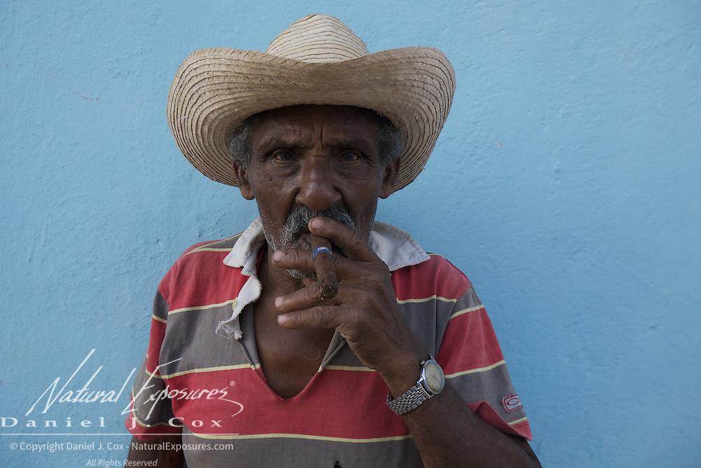 Man smoking a cigar on the streets of Trinidad, Cuba.