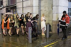 © Licensed to London News Pictures . 17/03/2013 . Manchester , UK . People queue for a cab in the rain . Evening revellers out in the rain and snow in to the early hours , in Manchester this St Patrick's Day morning (17th March) . Photo credit : Joel Goodman/LNP