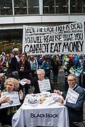 Activists stage a mock dinner and eat fake money outside the offices of Blackrock asset managers during a protest in the City of London, on 14th October 2019. Hundreds of activists blocked roads  in the financial district on Monday, calling out the financial sectors funding of fossil fuels around the world.