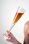 young Woman's shoulder arm and hand holding a cocktail glass at an event