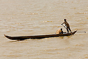 17 MARCH 2006 - KAMPONG CHHNANG, KAMPONG CHHNANG, CAMBODIA: A man and boy paddle a canoe on the Tonle Sap River in the city of Kampong Chhnang in central Cambodia. PHOTO BY JACK KURTZ