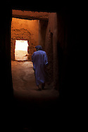 Man dressed in a traditional moroccan gandora walks through a Kasbah.