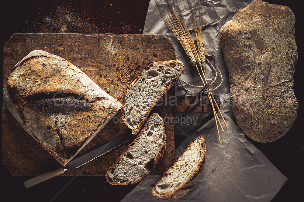 Bread loafs whole and sliced on rustic wooden board and paper sheets, with wheat ears and knife, top view.