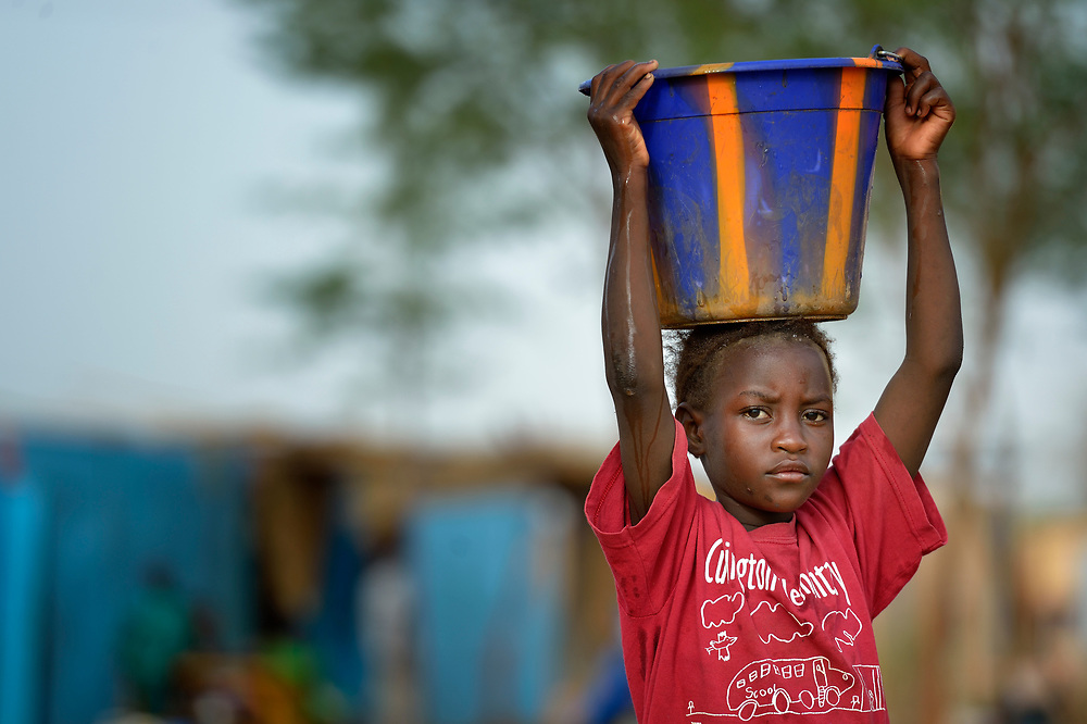 Eight-year old Sisi Maiga carries water in a camp in Mopti, Mali, for families displaced by the fighting in the north of the country. Islamist rebels seized control of Maiga's home town of Gossi and other areas of the north in 2012, but were chased out in early 2013 by French troops. Many displaced and refugee families have yet to return, preferring to wait for better security and improved economic conditions in the north.