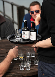 Tourists sampling rare single malt whisky at Bunnahabhain Distillery on island of Islay in Inner Hebrides of Scotland, UK