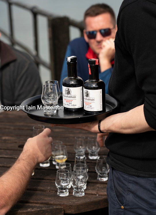 Tourists sampling rare single malt whisky at Bunnahabhain Distillery on island of Islay in Inner Hebrides of Scotland, UK