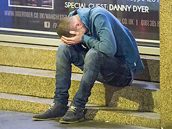 © Licensed to London News Pictures . 01/01/2015 . Manchester , UK . A man , ejected from Tiger Tiger, sits on steps with his head in his hands . He is missing special guest Danny Dyer . Revellers usher in the New Year on a night out in Manchester City Centre .  Photo credit : Joel Goodman/LNP