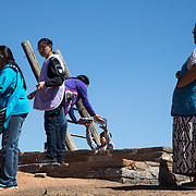 Food is handed down to the men in the kiva, March 24, 2019, Moenkopi, Arizona. It's the groom's responsibility to help gather the materials needed for the robe and the reeds for the wedding suitcase. They are both made inside the kiva, a traditional structure built underground and used for ceremonies by the Hopi people. The length of the wedding varies, depending on how long it takes for the bride's robes and suitcase to be completed. Weaving starts on the first day of the wedding when the bride arrives at her in-laws' house, and she stays until they're completed, so she can wear them on her return journey home.