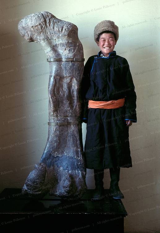 A school boy in a tradional dell (or deel) on a class tour stands proud with a sauropod femur on display at the Ulan Bator State Museum in Mongolia.