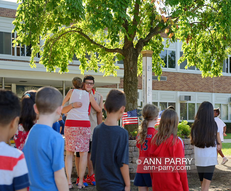 North Merrick, New York, U.S. September 11, 2019. At Park Avenue School, a teacher hugs NICHOLAS CARRANO, 15, of Merrick, a member of Boy Scout Troop 123, as her students walk around the 9/11 Memorial Garden on their way back into school after 9/11 ceremony, on 18th Anniversary of terrorist attacks Sept. 11, 2001.