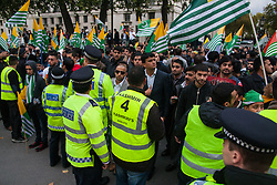 Trafalgar Square, London, October 26th 2014. Thousands of Kashmiris in London demonstrate in Trafalgar Square before marching to Downing Street to deliver a petition asking for Britain's support in ending the occupation of Kashmir by India. PICTURED: Police drive the peaceful but spirited crowd to the side of Whitehall.