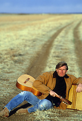 handsome All American man with a guitar sitting on a dirt road